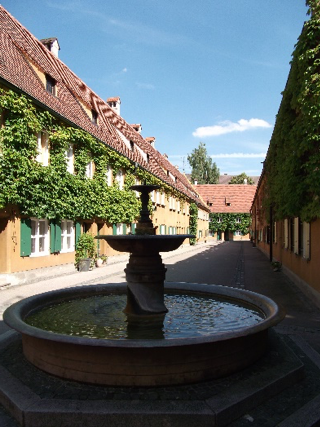 A street inside the Fuggerei showing the rows of 'almshouses' and the bronze bust of Jacob Fugger in the Fuggerei